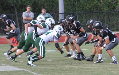 The Hawks' offensive line protects against the Kinghts' defense. (Photo by Matt Harris)